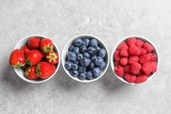 Bowls with raspberries, strawberries and blueberries. On table, top view stock photos