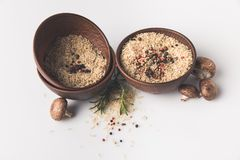Raw rice with spices and mushrooms on white tabletop stock image