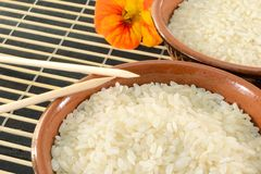 Bowls of rice. Close up of bowls of white rice,two chopstick on a bamboo mat stock photo