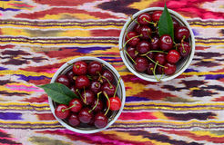 Bowls with ripe cherry over bright oriental tablecloth Stock Images