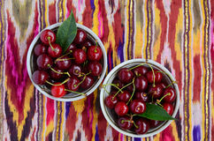 Bowls with ripe cherry over traditional asian pattern fabric Royalty Free Stock Photos