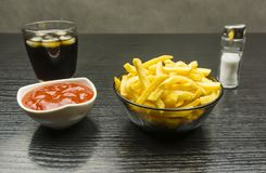 Bowls with salted french fries and ketchup and a glass of cola w stock images
