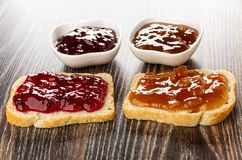 Bowls and sandwiches with currant jam, apricot jam on table. Bowls and sandwiches with currant jam, apricot jam on dark wooden table royalty free stock photo