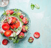 Bowls with  sliced Strawberries with powdered sugar and mint leaves on light blue rustic background. Top view Royalty Free Stock Photo