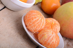 Bowls of slices mandarin with apple on rustic wooden background Stock Photography
