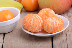 Bowls of slices mandarin with apple on rustic wooden background Stock Photos