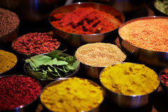 Bowls of spices. Some metal bowl filled with an assortment of different coloured spices royalty free stock photography