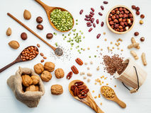 Bowls and spoons of various legumes and different kinds of nuts Royalty Free Stock Image