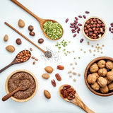 Bowls and spoons of various legumes and different kinds of nuts Royalty Free Stock Photography