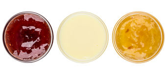 Bowls with strawberry, lemon jam and condensed milk on white Stock Photography