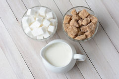 Bowls of Sugar and Cream. High angle shot of two bowls of sugar cubes, white and natural, and a pitcher filled with cream. Horizontal format on a rustic wood Stock Images