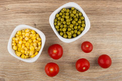 Bowls with sweet corn, green peas and tomato cherry. On wooden table. Top view Stock Photos