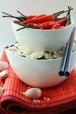 Bowls of uncooked rice and chili peppers Royalty Free Stock Image