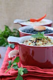Bowls of uncooked rice and chili peppers Stock Images