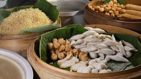 Bowls with various Asian dishes in diner. Wooden bowls with assorted traditional Thai dishes for sale placed on stall of stock footage