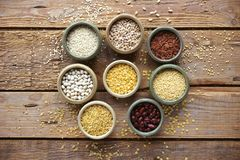Bowls of various cereals in small containers on a wooden background, Cereal Mix, Beans, sesame, rice, pearl barley, wheat, Closeup Stock Photo