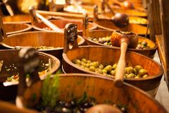 Bowls of various olives for sale at a market place.  stock photo