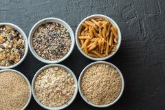 Bowls with whole grain carbohydrates, oats, brown rice, seeds, quinoa and whole grain pasta. Whole grain cereals. Bowls with whole grain carbohydrates, oats Stock Image
