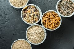 Bowls with whole grain carbohydrates, oats, brown rice, seeds, quinoa and whole grain pasta. Whole grain cereals. Bowls with whole grain carbohydrates, oats Stock Photo