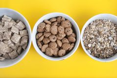 Bowls of whole grain muesli, granola and oatmeals with copy space. Isolated on yellow background. Top view. Daily breakfast food. royalty free stock images