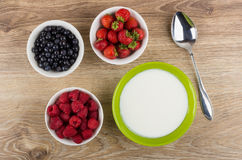 Bowls with yogurt, blueberries, raspberries, strawberries and sp Stock Photos