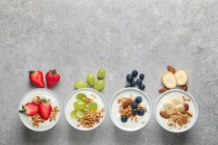 Bowls with yogurt, granola and different fruits. On gray background, top view royalty free stock photos