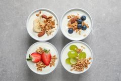 Bowls with yogurt, granola and different fruits. On gray background, top view royalty free stock image