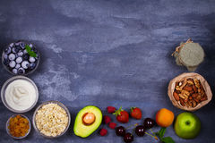 Bowls of Yogurt and Oat Flakes, Fruits, Honey and Summer Berries. View from above, top studio shot of fruit background. Flat lay setup made of selection of Stock Photo