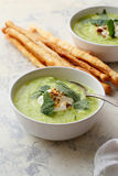 Bowls of zucchini cream soup and bread sticks Royalty Free Stock Images