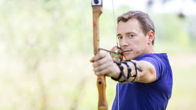 Bowman aiming arrow at target Stock Photos
