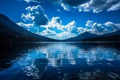 Bowron Lakes View. Day shot of Bowron Lakes, Canada. Cumulus Clouds mirror in lake Royalty Free Stock Image