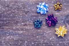 Bows for gifts on a wooden surface with snowflakes. Christmas background with multi-colored bows. stock photos