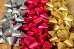 Bows of three colors for gifts. Bows for gifts of three colors over wooden table Royalty Free Stock Photos