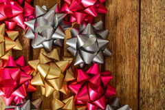 Bows of three colors for gifts. Bows for gifts of three colors over wooden table, top view Royalty Free Stock Images