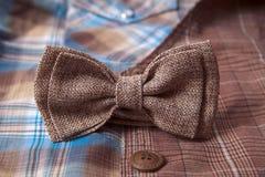 Bowtie и кольца на предпосылке одежды из твида ткани костюма ткани серой Стоковая Фотография