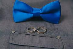 Bowtie и кольца на предпосылке одежды из твида ткани костюма ткани серой Стоковое Изображение