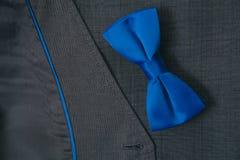 Bowtie и кольца на предпосылке одежды из твида ткани костюма ткани серой Стоковая Фотография RF