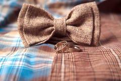 Bowtie и кольца на предпосылке одежды из твида ткани костюма ткани серой Стоковые Фото