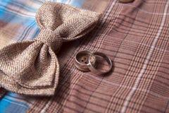 Bowtie и кольца на предпосылке одежды из твида ткани костюма ткани серой Стоковое Изображение RF