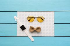 Bowtie and spectacles with smartwatch on paper stock image