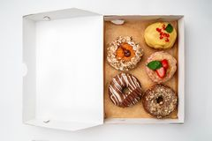 Box with assortment of donuts. Top view. Space for text stock image