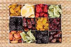 Box with assortment of dried fruits closeup on beige mat background. Stock Photo