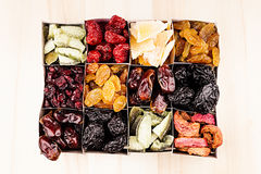 Box with assortment of dried fruits closeup on beige wooden background. Royalty Free Stock Images