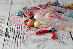 Box with beads, plier and glass hearts to create hand made jewel Royalty Free Stock Image