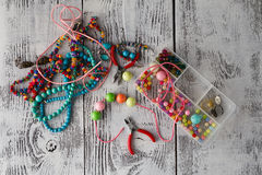 Box with beads, plier and glass hearts to create hand made jewel Royalty Free Stock Photo