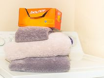 A box of Bounce dryer sheets is placed on clean folded towels - Front view stock image