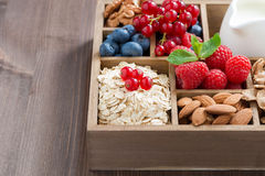 Box with breakfast items - oatmeal, granola, nuts and berries. Box with breakfast items - oatmeal, granola, nuts, berries and milk on wooden table, horizontal Royalty Free Stock Images