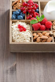 Box with breakfast items - oatmeal, granola, nuts and berries. Box with breakfast items - oatmeal, granola, nuts, berries and milk on wooden table, vertical, top Stock Photo