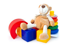 Box of bricks with a teddy bear and a pyramid. Colorful box of bricks with a teddy bear and a pyramid. Developing children's toys Royalty Free Stock Photo