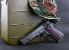 Box for bullets, a gun and a camouflaged hat Stock Photos